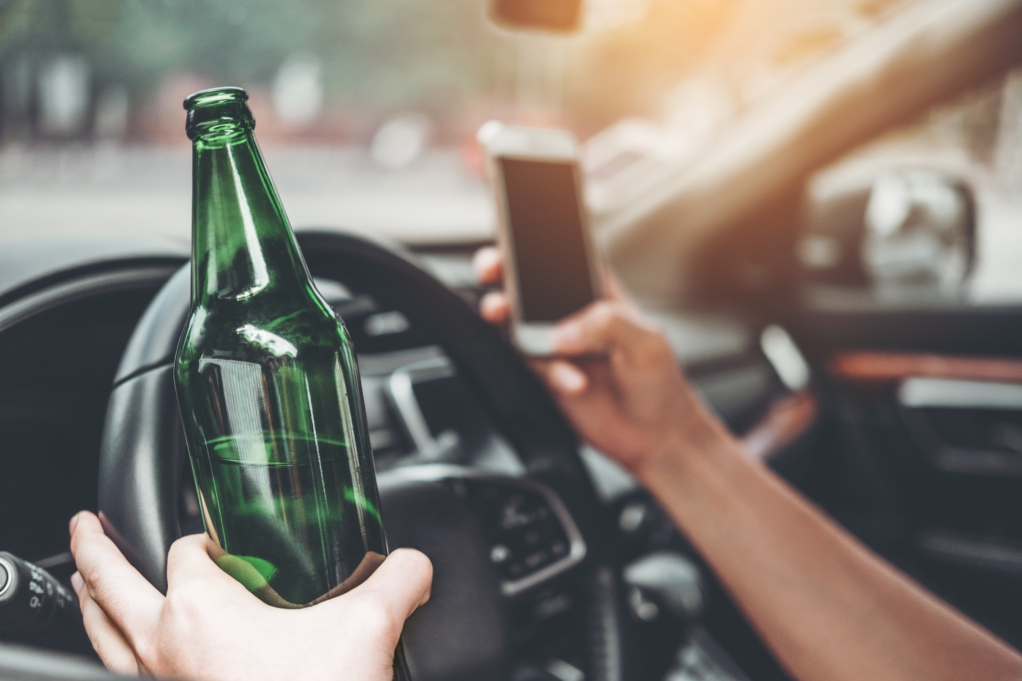 Drunk man driving a car on the road holding bottle beer Dangerous drunk driving concept