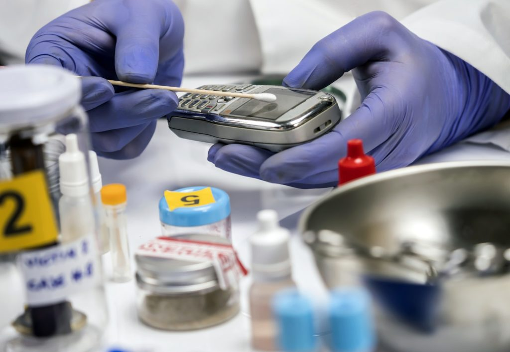 Specialist police take DNA sample from murder victim's mobile phone, conceptual image